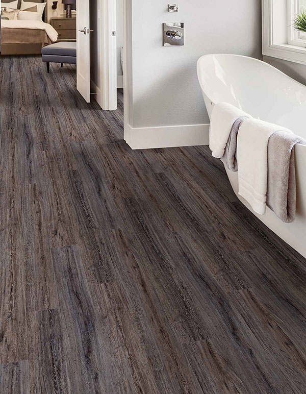Close up image of a trending 2020 floors utilizing luxury vinyl tiles (LVT) and a large white soaking tub.